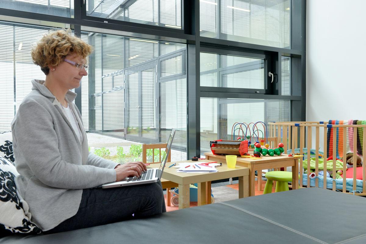 Eine Frau sitzt am Laptop und arbeitet in einem Familienzimmer