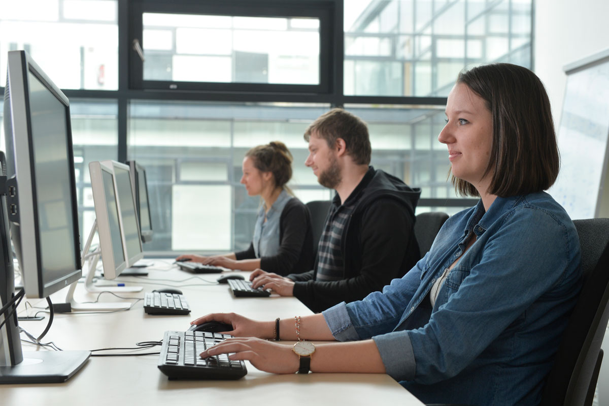 Drei junge Leute sitzen vor Bildschirmen und arbeiten