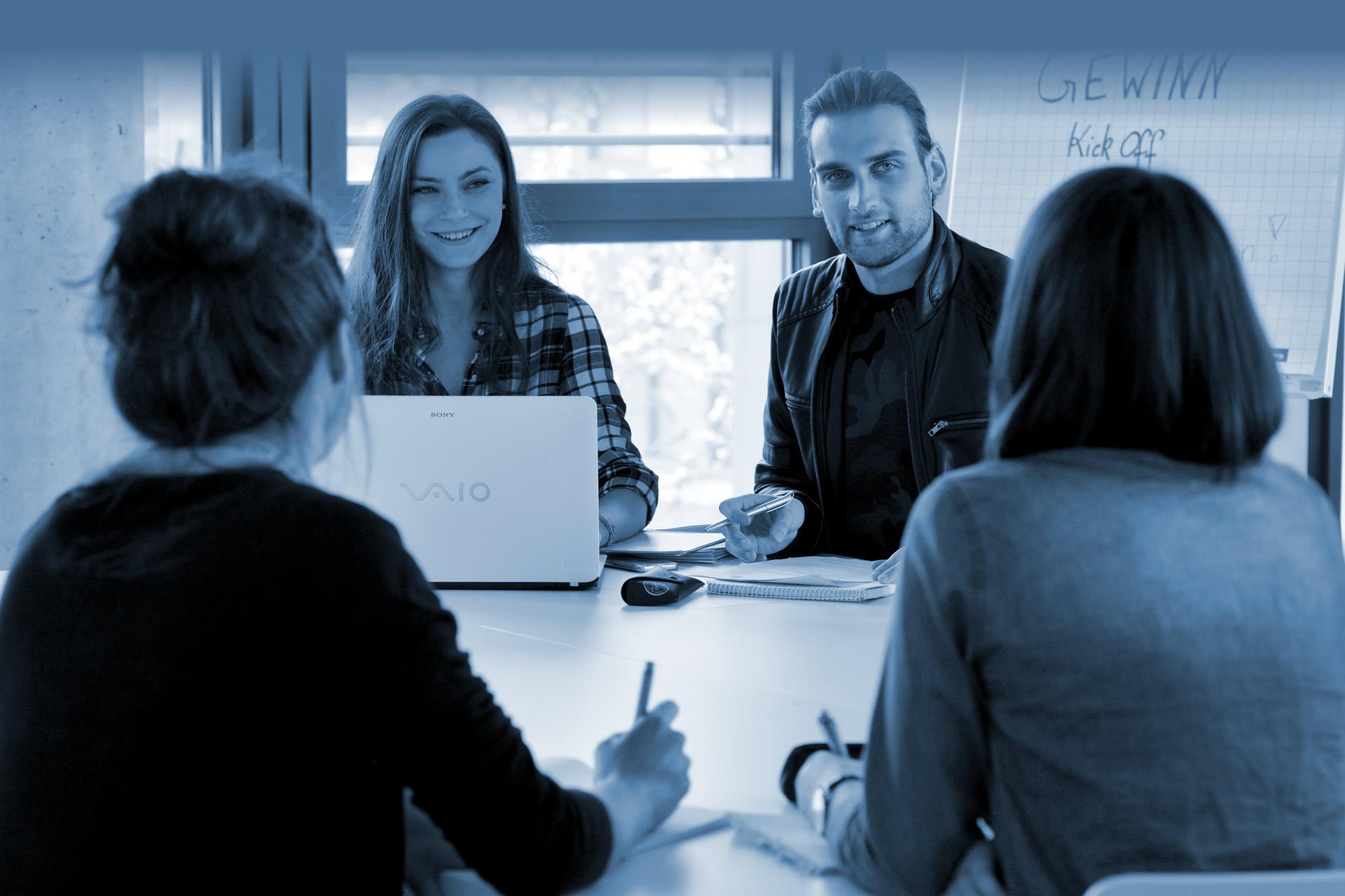 Studierende arbeiten gemeinsam sitzend an einem Tisch