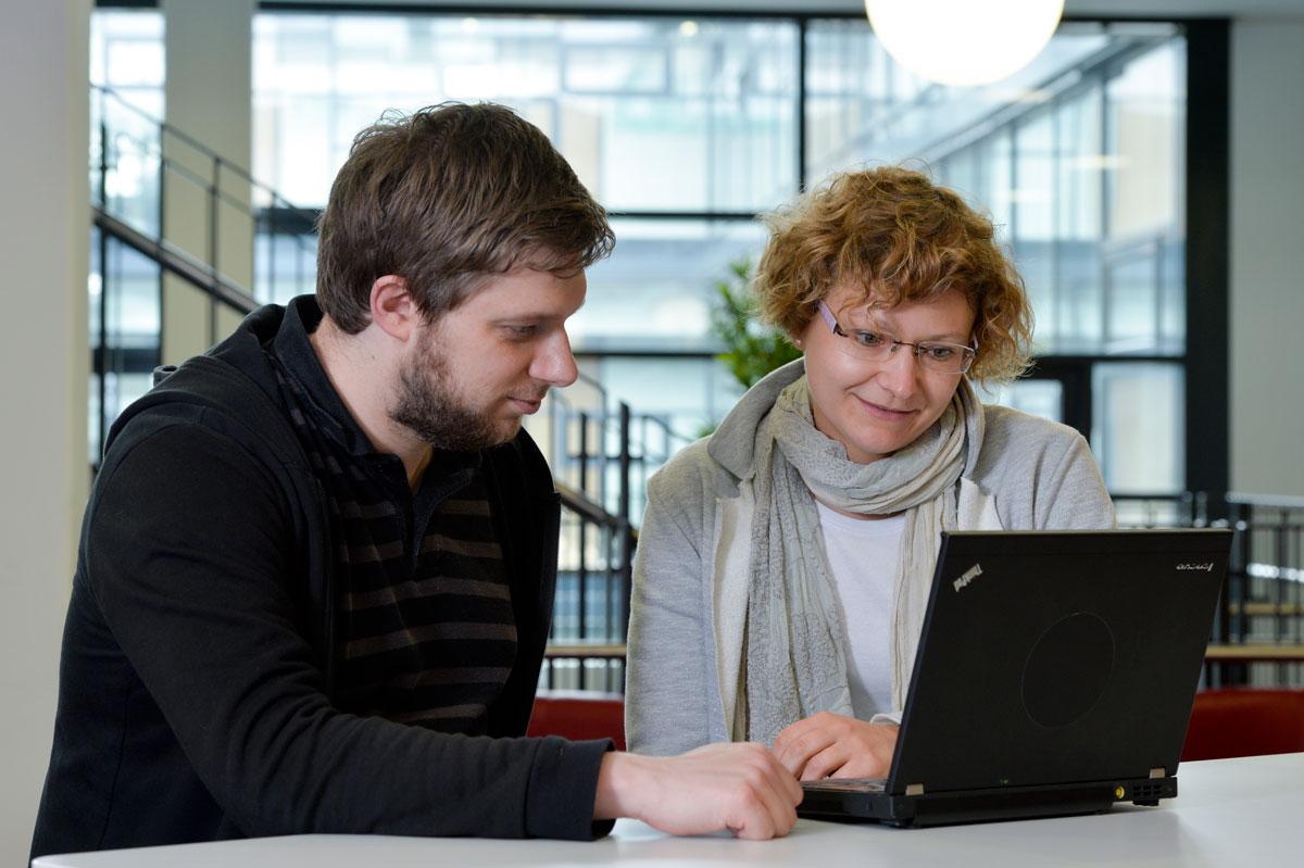 Ein Mann und eine Frau sitzen an einem Tisch und schauen gemeinsam auf den Bildschirm eines Laptops