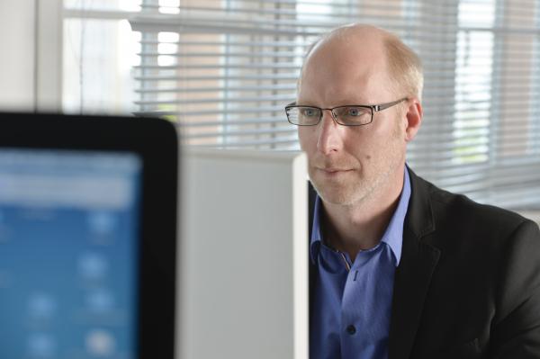 Ein Mann sitzt vor einem Bildschirm und arbeitet
