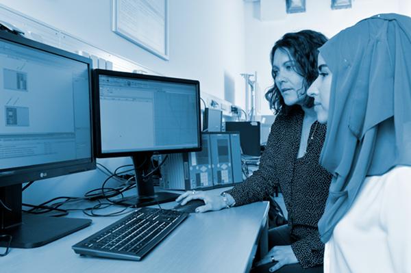 Zwei Frauen sitzen an einem Schreibtisch und sehen auf zwei Computerbildschirme.