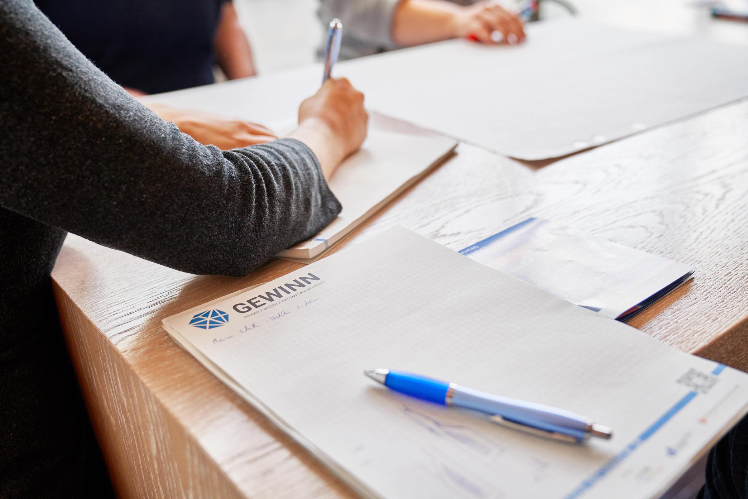 Ein Block und ein Stift mit dem Logo des Projekt GEWINN liegen auf dem Tisch, daneben schreibt jemand.