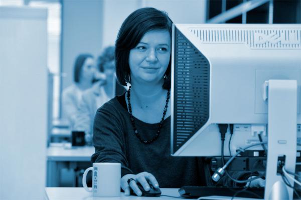 Frau sitzt am Schreibtisch und schaut auf einen Computerbildschirm.
