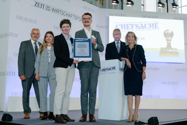 Sechs Personen stehen auf dem Podium und zeigen die Urkunde zur Preisverleihung Chefsache Award 2017